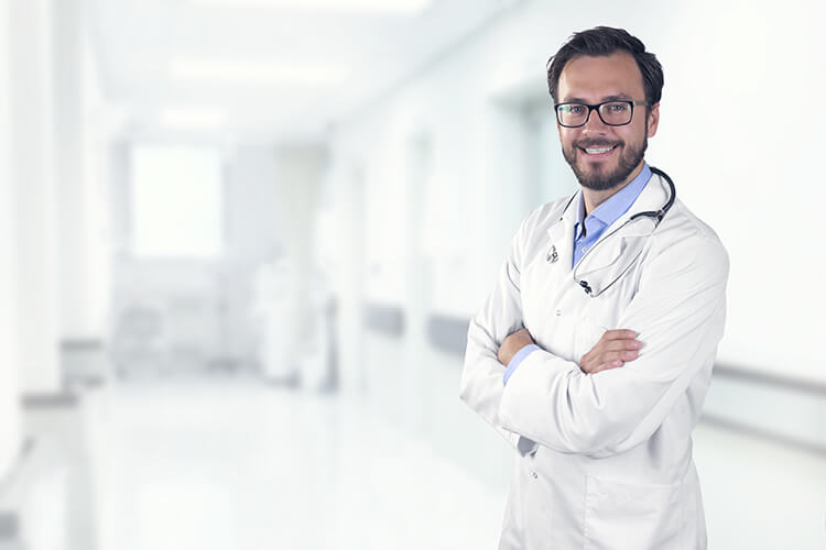 Physician with crossed arms standing in empty hospital hallway