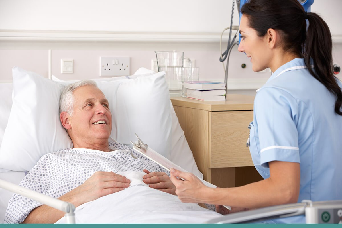 Healthcare worker sitting beside a patient's bed reading from a clipboard