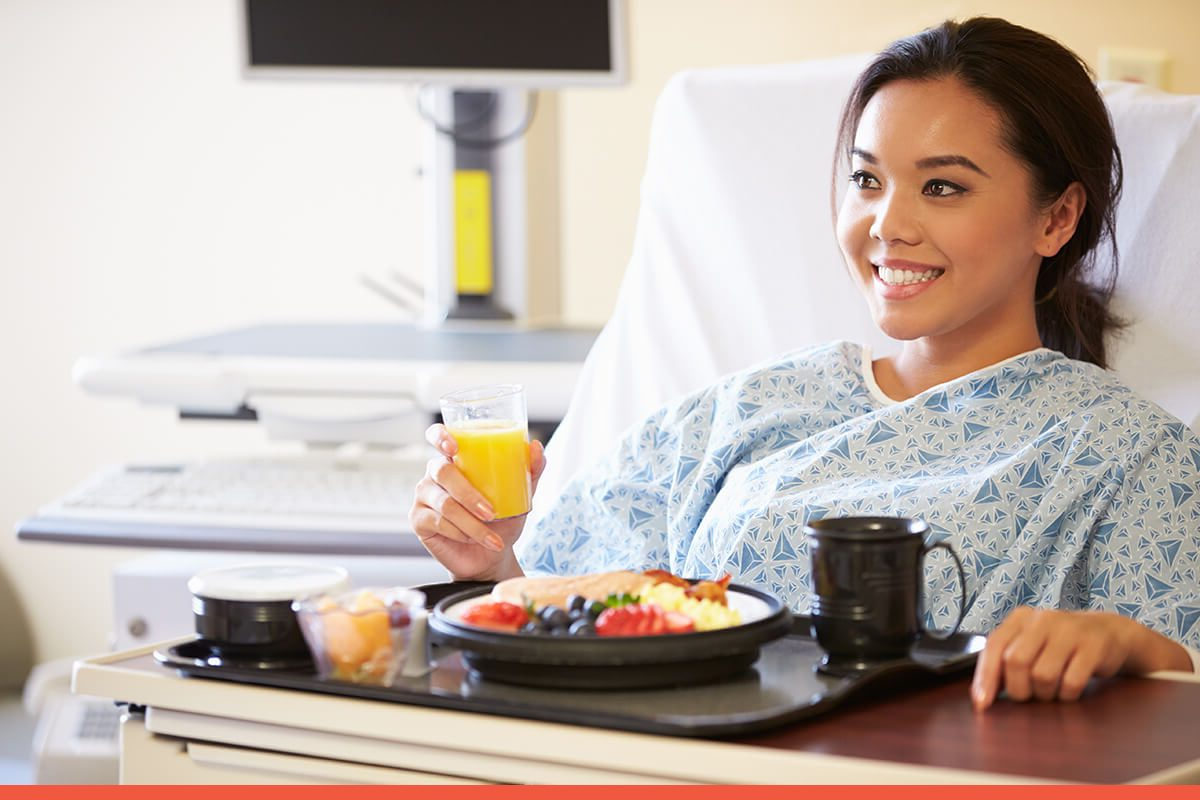 Female patient sitting in a hospital bed with a tray of breakfast