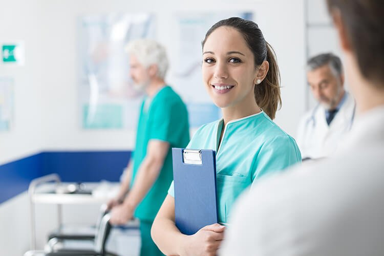 Healthcare provider standing in busy hospital with clipboard