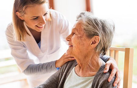 Nurse leaning over an elderly woman's shoulder speaking with her