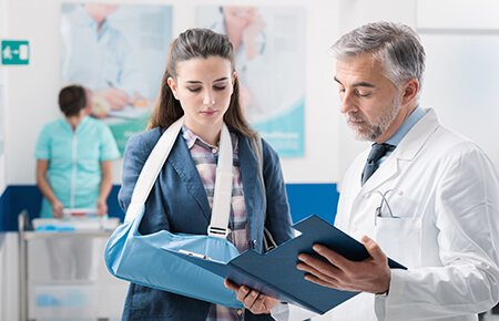 Physician reviewing chart with woman in arm sling