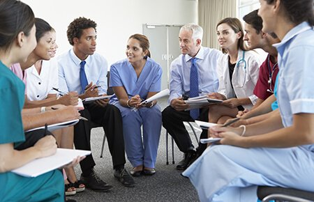 Group of clinicians sitting in a circle participating in training session